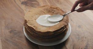 Ausgebreiteter Sauerrahm auf Pfannkuchen oder Blini Lizenzfreie Stockbilder