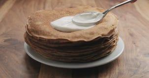 Ausgebreiteter Sauerrahm auf Pfannkuchen oder Blini Lizenzfreies Stockfoto