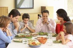 Ausgedehnte hispanische Familie, die zu Hause Gebete vor Mahlzeit sagt Stockfoto
