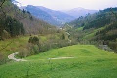 Ausgedehntes heraus Tal in den Bergen mit einer kurvenreichen Straße lizenzfreie stockfotos