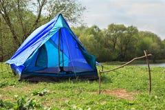 Ausgefahrenes Zelt steht auf Flussquerneigung stockfotografie