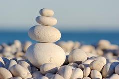 Ausgeglichene Kiesel auf Küste Stockfoto