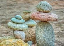 Ausgeglichene Staplungsfelsen auf einem sandigen Strand Stockfotografie