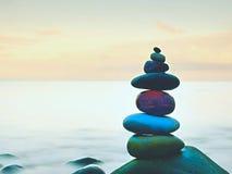 Ausgeglichene Steine, Zen Stack vor glattem Ozean Eine beruhigende Ansicht von der Terrasse stockfoto