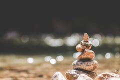 Ausgeglichenes Stein-pyramide auf Ufer auf einem Strom der Natur verwischte Hintergrund bokeh Stockbild