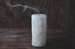 Ausgelöschte große Kerze in der Dunkelheit Auf einem h?lzernen Hintergrund Kerzenrauch stockfoto