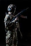 Ausgerüsteter Soldat, der im Profil steht und Automaten oben angehoben hält stockfotografie