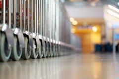 Ausgerichtete Laufkatzen am Flughafen Kofferkulis am Flughafen stockbilder