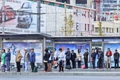 Ausgerichtete Leute an Bus staion, Dalian, China Stockbild