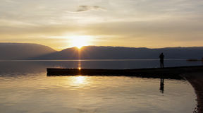 Ausgezeichnete Landschaft bemannen Sie die Abbildung des Sonnenuntergangs über See prespa in Macedonia Lizenzfreie Stockfotos