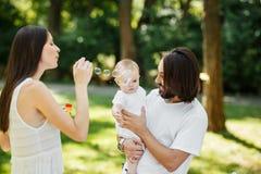 Ausgezeichnete Mutter, die Seifenblasen macht Vater mit kleiner netter Tochter in den Armen betrachten es und das Lächeln lizenzfreie stockfotos