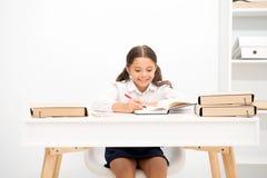 Ausgezeichnete Pupille Mädchenkind schreibt hometask, während Tabellenweißhintergrund sitzen Sie Schulmädchen, das Schreibensvers lizenzfreies stockfoto