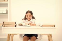 Ausgezeichnete Pupille M?dchenkind schreibt hometask, w?hrend Tabellenwei?hintergrund sitzen Sie Schulm?dchen, das Schreibensvers stockfoto