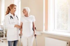 Ausgezeichneter ausgebildeter Doktor, der während der Rehabilitation unterstützt stockbild