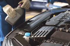 Ausgezeichneter erfahrener Mechaniker, der Motorenöl verwendet Lizenzfreie Stockfotografie
