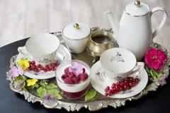 Ausgezeichneter frischer heißer Tee in den alten Schalen auf einem silbernen Weinlesebehälter und einem Himbeernachtisch, eine an stockbild