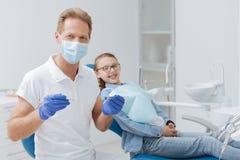 Ausgezeichneter lokaler Zahnarzt, der Berufswerkzeuge in seinem Arbeit einsetzt Stockbild