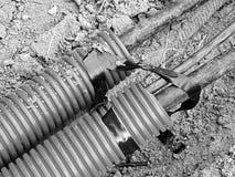 Aushöhlung des Grabens mit schwarzen Kabeln im schützenden HDPE-Rohr Linien von metallischem und Faseroptikdrähte Lizenzfreies Stockbild