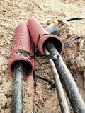 Aushöhlung des Grabens mit schwarzen Kabeln im schützenden HDPE-Rohr Linien von metallischem und Faseroptikdrähte Lizenzfreie Stockbilder
