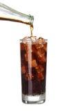 Auslaufende Cola der Flasche im Getränkglas mit den Eiswürfeln lokalisiert Stockbilder