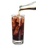 Auslaufende Cola der Flasche im Getränkglas mit den Eiswürfeln lokalisiert Lizenzfreie Stockfotos