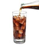 Auslaufende Cola der Flasche im Getränkglas mit den Eiswürfeln lokalisiert Lizenzfreies Stockbild