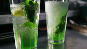 Auslaufende Limonade des Schankwirtes in Glas mit Eis, Zitrone, Minze und Sirup stock footage