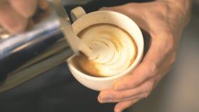 Auslaufende Milch Barista, im Kaffee und Latteschaum im Kaffeestubeabschluß in bilden stockfoto