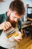 Auslaufende Milch Barista in Tasse Kaffee stockfotos