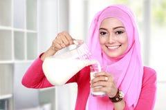 Auslaufende Milch der jungen moslemischen Frau in ein Glas Stockfotografie