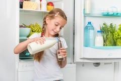Auslaufende Milch des kleinen Mädchens im Glas Stockfotos