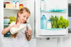 Auslaufende Milch des kleinen Mädchens im Glas Stockbilder