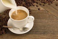 Auslaufende Milch in einem Tasse Kaffee Stockfotos