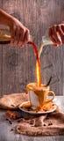Auslaufende Milch in einen Tasse Kaffee Stockbild