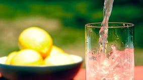 Auslaufende rosa Limonade in eine Glaszeitlupe stock video