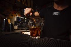 Auslaufender Alkohol des Barmixers in ein Glas Stockfotografie