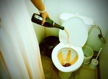 Auslaufender Champagner der Frau in der Toilette Lizenzfreie Stockfotografie