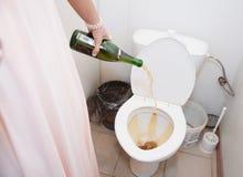 Auslaufender Champagner der Frau in der Toilette Stockfotos
