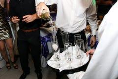 Auslaufender Champagner des Kellners in den Gläsern an der Hochzeit stockfotos