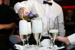 Auslaufender Champagner des Kellners in den Gläsern an der Hochzeit lizenzfreie stockbilder