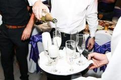 Auslaufender Champagner des Kellners in den Gläsern an der Hochzeit stockbild
