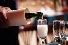 Auslaufender Champagner in ein Glas Stockfoto