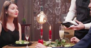 Auslaufender Champagner in einem leeren Glas während Gespräche und Lächeln junger Dame stock video