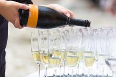 Auslaufender Champagner in Gläser Stockfotografie