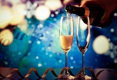 auslaufender Champagner in Gläser gegen Lichterkette Lizenzfreies Stockfoto