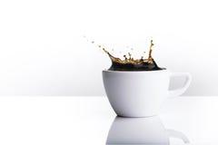 Auslaufender Kaffee auf dem weißen Hintergrund Lizenzfreies Stockfoto