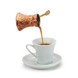 Auslaufender Kaffee des kupfernen Kaffeetopfes in einer weißen keramischen Kaffeetasse Lizenzfreies Stockbild