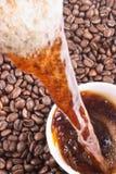 Auslaufender Kaffee und Kaffeebohnen Lizenzfreies Stockbild
