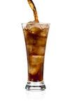 Auslaufender Sodakolabaum in einem Glas mit Eis auf Weiß Lizenzfreies Stockfoto