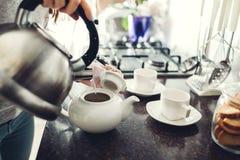 Auslaufender Tee der Frau in keramische Schale bei Tisch lizenzfreie stockbilder